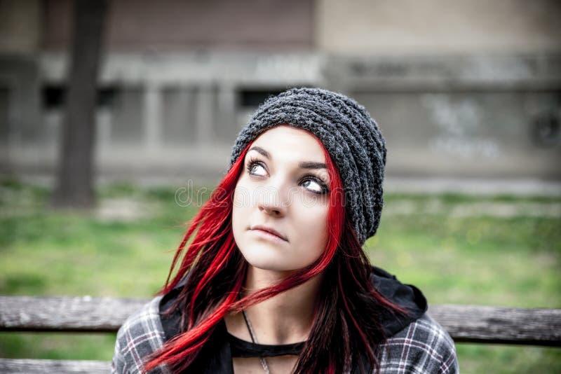 Dakloos meisje, Jong rood haarmeisje alleen in openlucht met hoed zitten en bezorgd en gedeprimeerd overhemd die nadat zij dakloz royalty-vrije stock fotografie