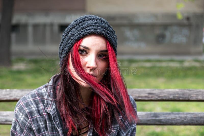 Dakloos meisje, Jong rood haarmeisje alleen in openlucht met hoed zitten en bezorgd en gedeprimeerd overhemd die nadat zij dakloz stock fotografie