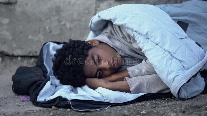 Dakloze afrikaanse tiener die in slaapzak ligt, armoedewerkloosheid stock afbeelding