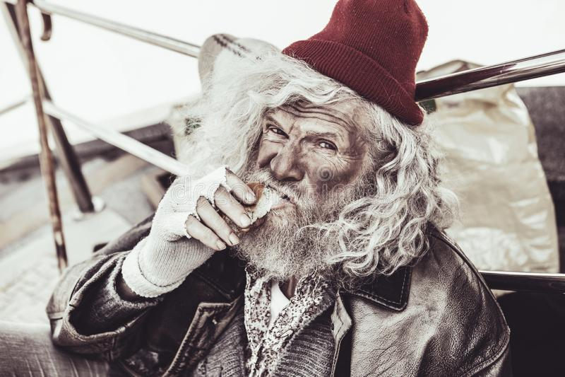 Dakloze bejaarden die broodje eten dat hij die voor aalmoes kopen en op de camera kijken royalty-vrije stock fotografie