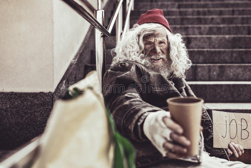 Dakloze bejaarden die zijn GLB waarvan hij aanbieden holding in één hand voor aalmoes stock foto