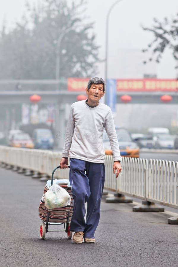 Dakloze bejaarden in smog bedekte stad, Peking, China royalty-vrije stock foto's