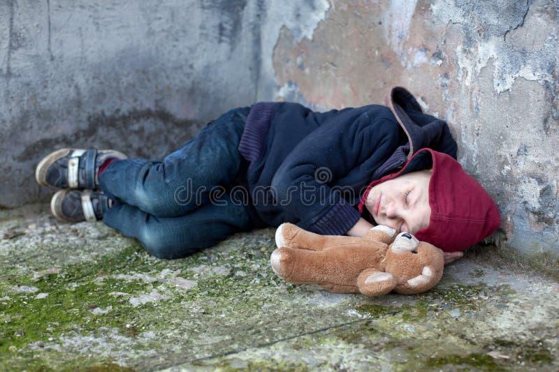 Dakloze die jongen tegen de muur wordt geleund stock fotografie