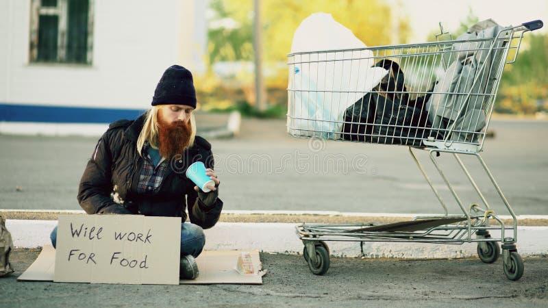 Dakloze jonge mens die hoeveel geld tellen hij holdingsdocument kop in de handen en zitting dichtbij boodschappenwagentje bij kre stock afbeeldingen