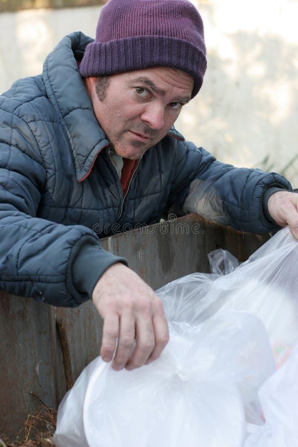 Dakloze Mens die - in Dumpster graaft royalty-vrije stock foto
