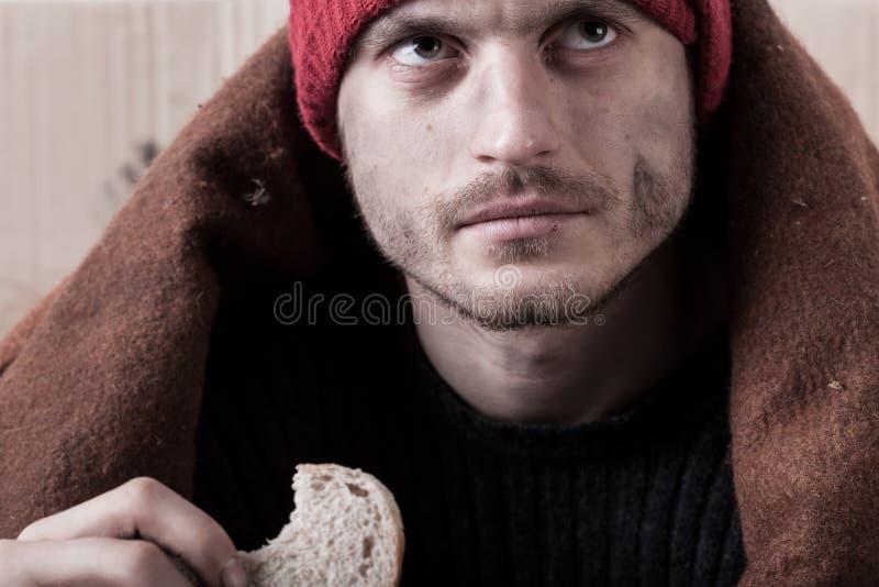 Dakloze mens die een stuk van brood eten royalty-vrije stock fotografie