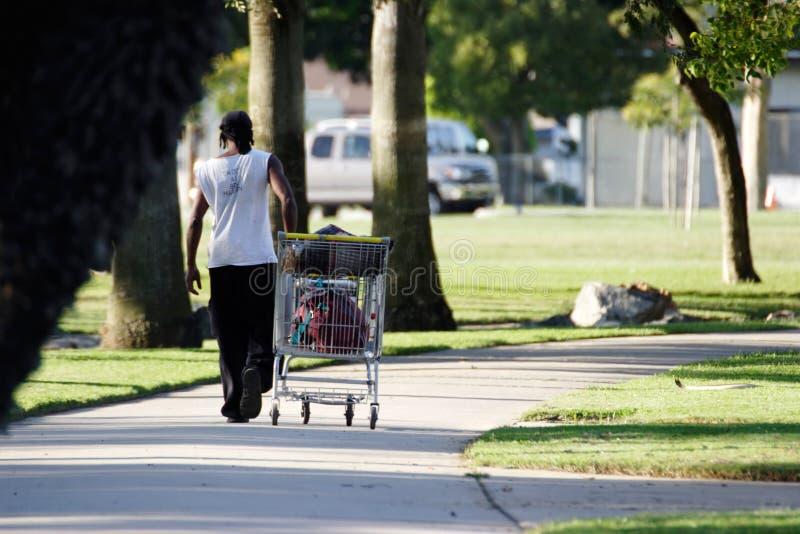 Dakloze mens met boodschappenwagentje stock fotografie