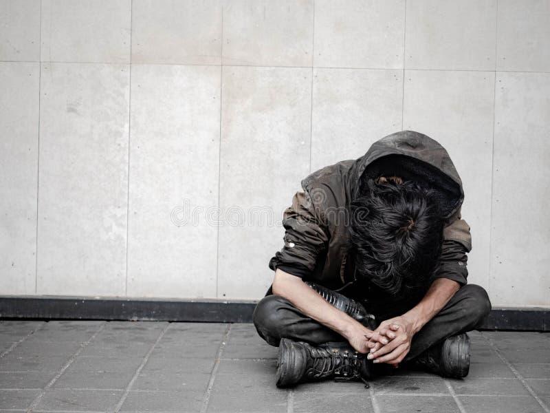 Dakloze mens op gangstraat in de stad en het bedelen voor hulp en geld Problemen van grote moderne steden royalty-vrije stock afbeelding