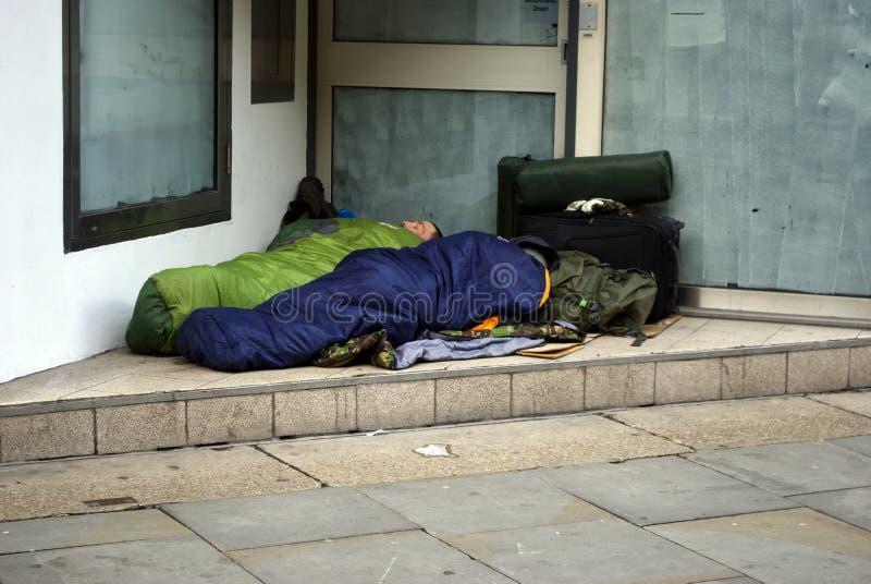Dakloze mensen die in een deuropening slapen stock afbeelding