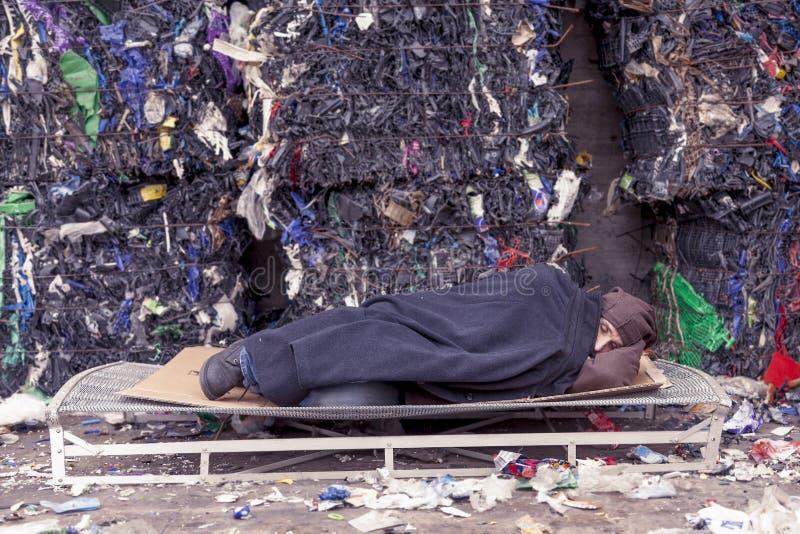 Dakloze mensenslaap in het afval royalty-vrije stock afbeeldingen