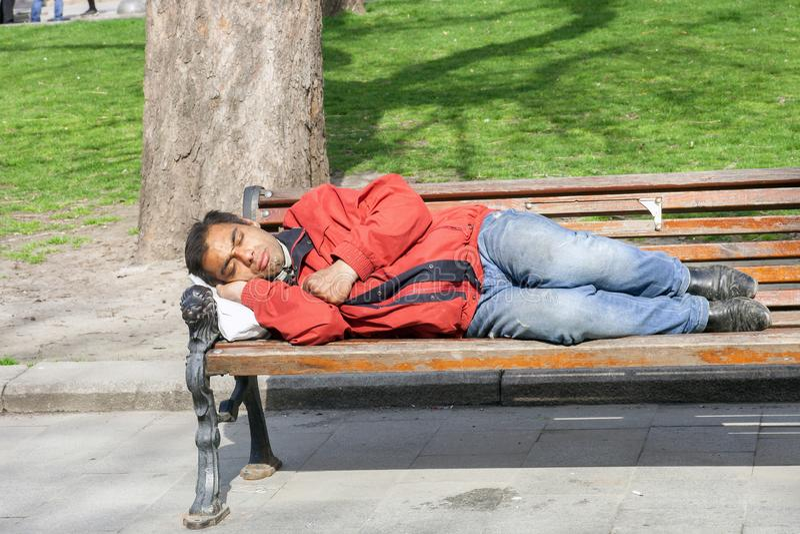 Dakloze mensenslaap op houten bank in park royalty-vrije stock foto