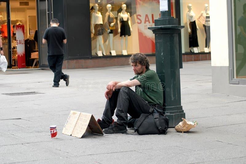 Dakloze mensenzitting op een straat met teken royalty-vrije stock foto's