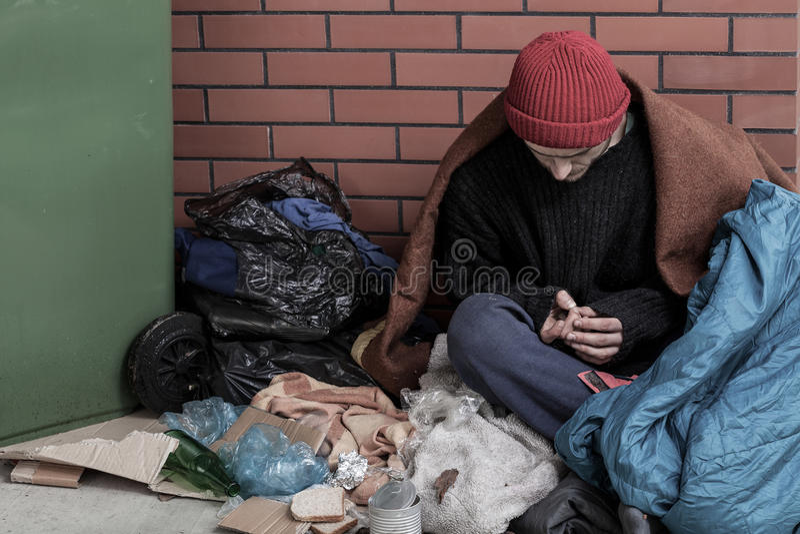 Dakloze mensenzitting op het afval royalty-vrije stock afbeeldingen