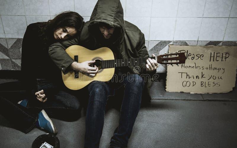 Dakloze Paarmens het Spelen Gitaar die om Geldschenking vragen stock foto