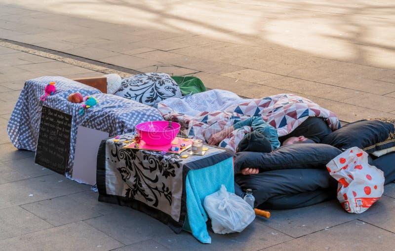 Dakloze paarslaap op de straat stock afbeeldingen