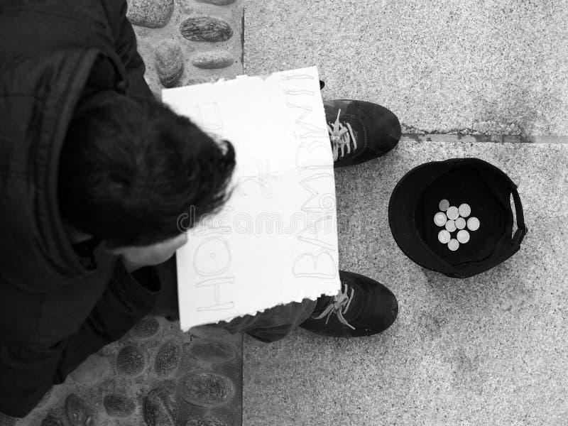 Dakloze persoon met karton stock afbeelding