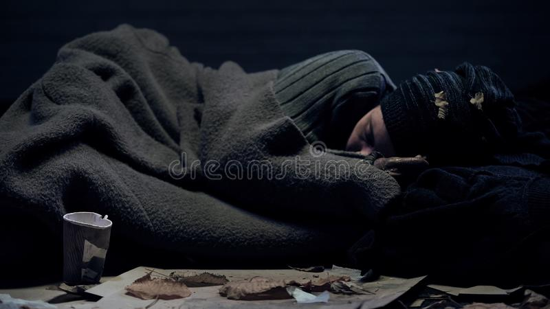 Dakloze persoon omvat door algemene slaap op stadsstraat, armoedeconcept stock fotografie