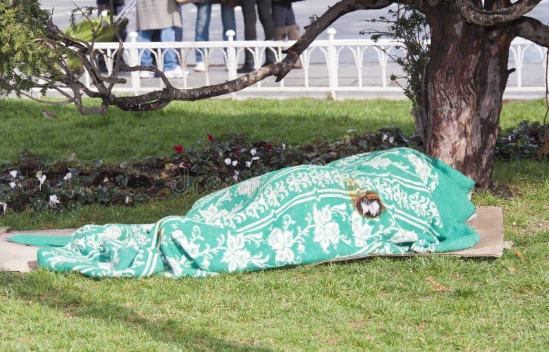 Dakloze persoonsslaap onder deken in park royalty-vrije stock foto