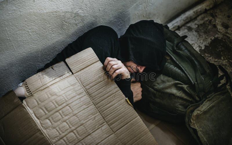 Dakloze persoonsslaap openlucht op de weg stock fotografie