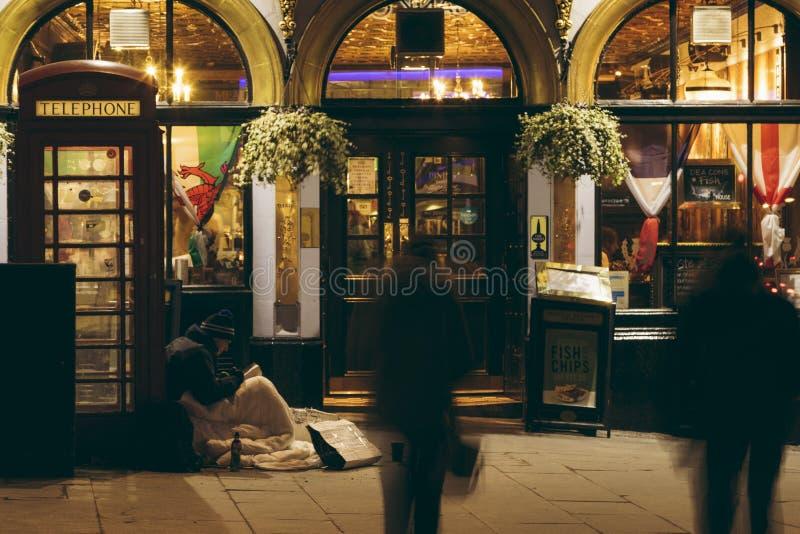 Dakloze persoonszitting buiten Diaken en de Herberg van Brodie ` s in ED stock foto