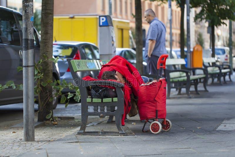 Dakloze slaap op een bank royalty-vrije stock afbeeldingen