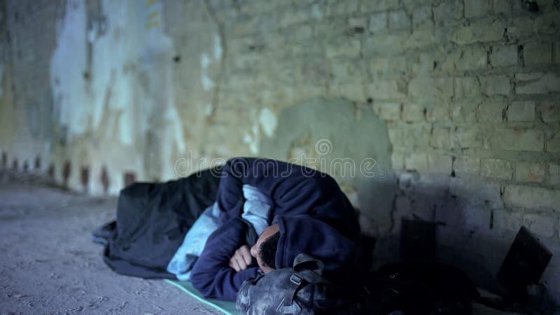 Dakloze tienerslaap op straat, armoede, de onverschillige egoïstische maatschappij stock fotografie