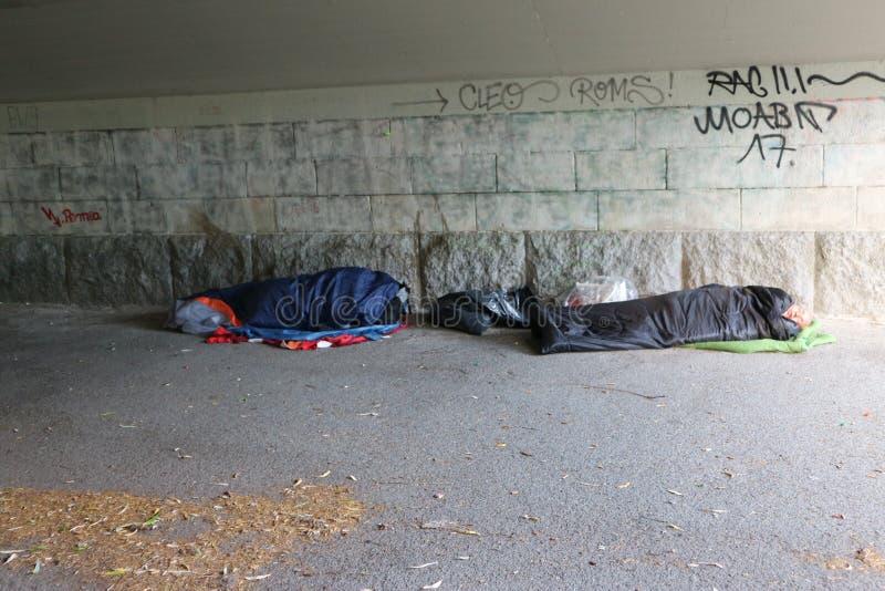 Dakloze vluchtelingen die in slaapzakken slapen royalty-vrije stock foto's