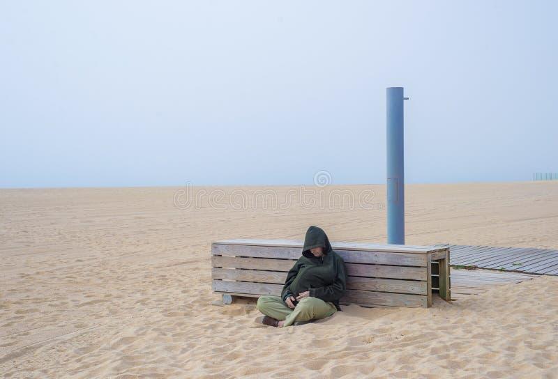 Dakloze volwassen mensenpersoon met kapzitting en slaap op zandig strand royalty-vrije stock foto