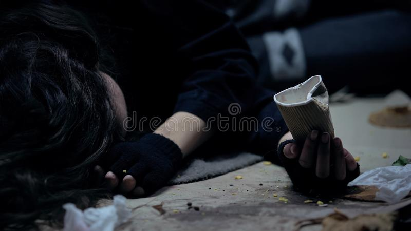 Dakloze vrouw met document kop die op grond in vuile plaats liggen, die voor geld bedelen royalty-vrije stock foto's