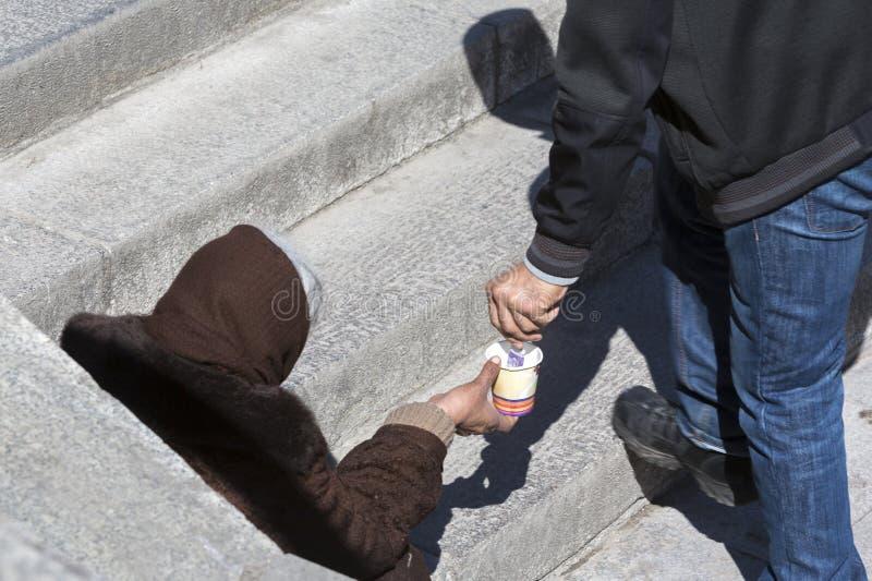 Daklozen die begger geld geven royalty-vrije stock afbeeldingen