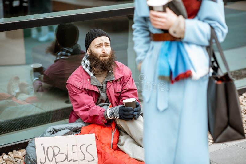 Daklozen die geld bedelen aan het overgaan door vrouw royalty-vrije stock afbeelding
