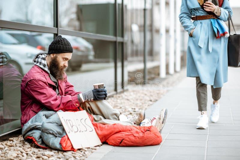 Daklozen die geld bedelen aan het overgaan door vrouw stock fotografie