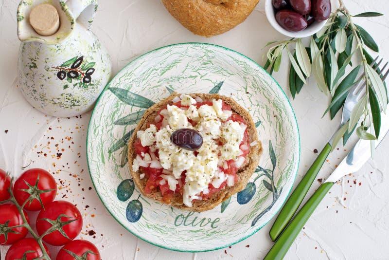 Dakos Greekappetizer traditionnel d'un plat traditionnel avec le pot en céramique d'huile d'olive, le pain de seigle sec, les oli photos stock