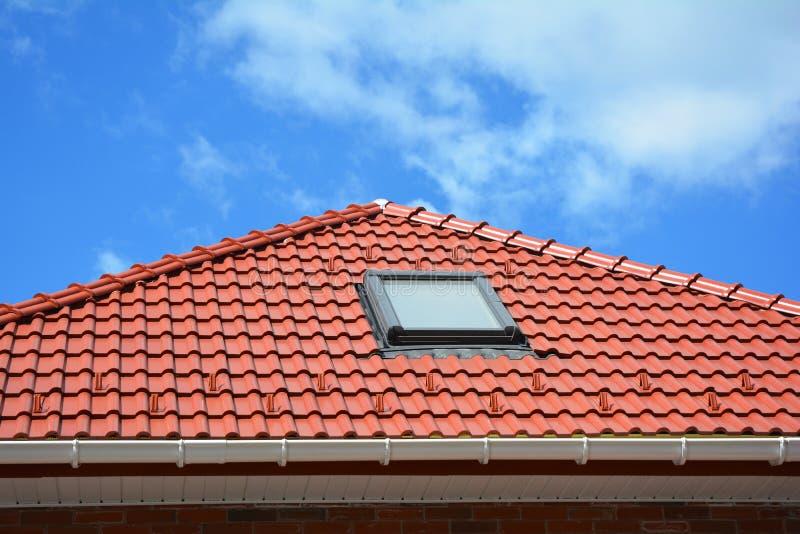 Dakraam op het rode dak van het keramische tegelshuis met dakgoot Dakramen, Dakvensters en Zontunnels Zolderdakraamoplossing royalty-vrije stock fotografie