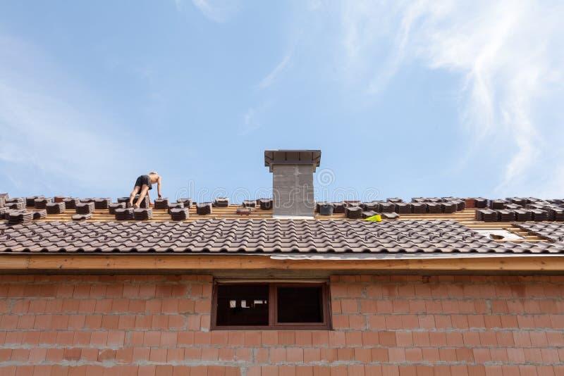 Dakwerk: bouwvakker op een dak die het behandelen met tegels - dakvernieuwing: installatie van teerdocument, nieuwe tegels en sch royalty-vrije stock foto