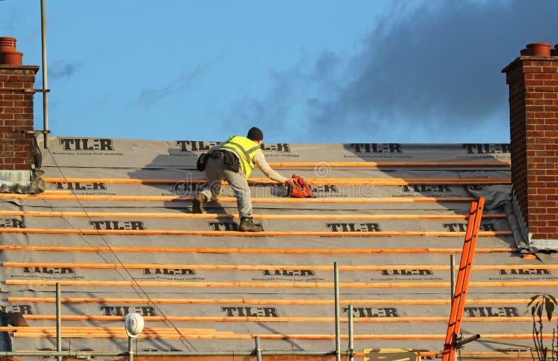 Dakwerk een huis Werkman die een dak bevestigen stock foto