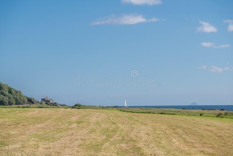 Dal Hawking Craig Woods alla baia di Portencross e Ailsa Craig nella distanza nebbiosa lontana con un singolo yacht che viene die immagine stock libera da diritti