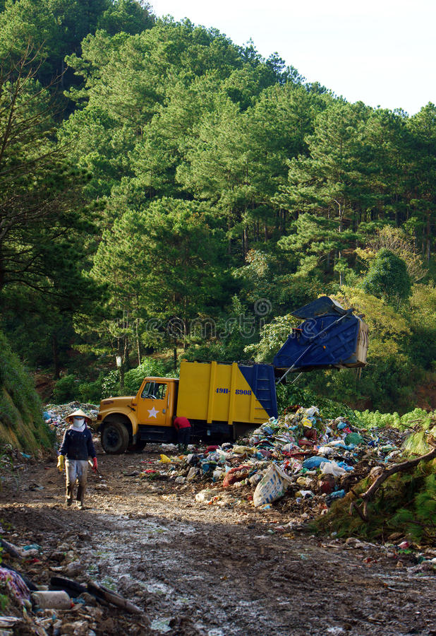 Garbage truck empty out the rubbish at dumping gro. Und. Dalat, Viet Nam- September 05, 2013 royalty free stock image