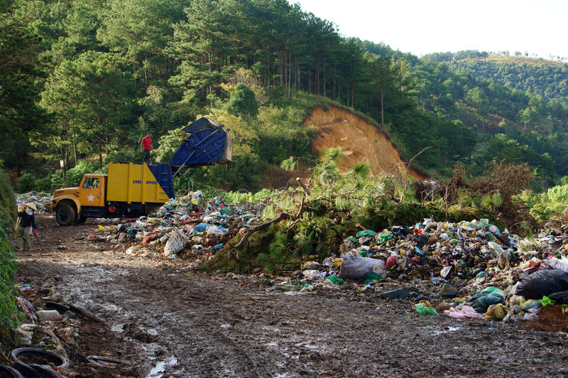 Garbage truck empty out the rubbish at dumping gro. Und. Dalat, Viet Nam- September 05, 2013 royalty free stock photography