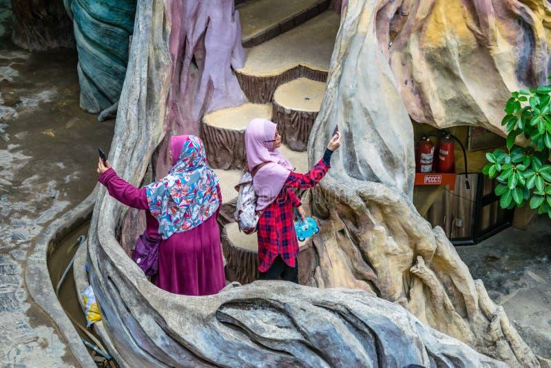 DALAT VIETNAM - APRIL 15, 2019: Arabiska kvinnor tar bilder på trappan i en härlig byggnad i galet hus i Dalat royaltyfri fotografi