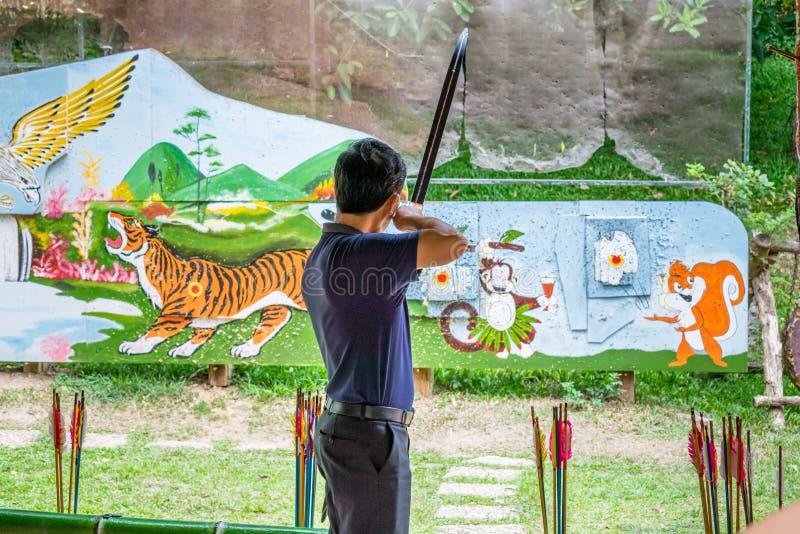 DALAT, VIETNAM - 15 APRILE 2019: Un uomo spara un arco ad un obiettivo con gli animali dipinti fotografia stock