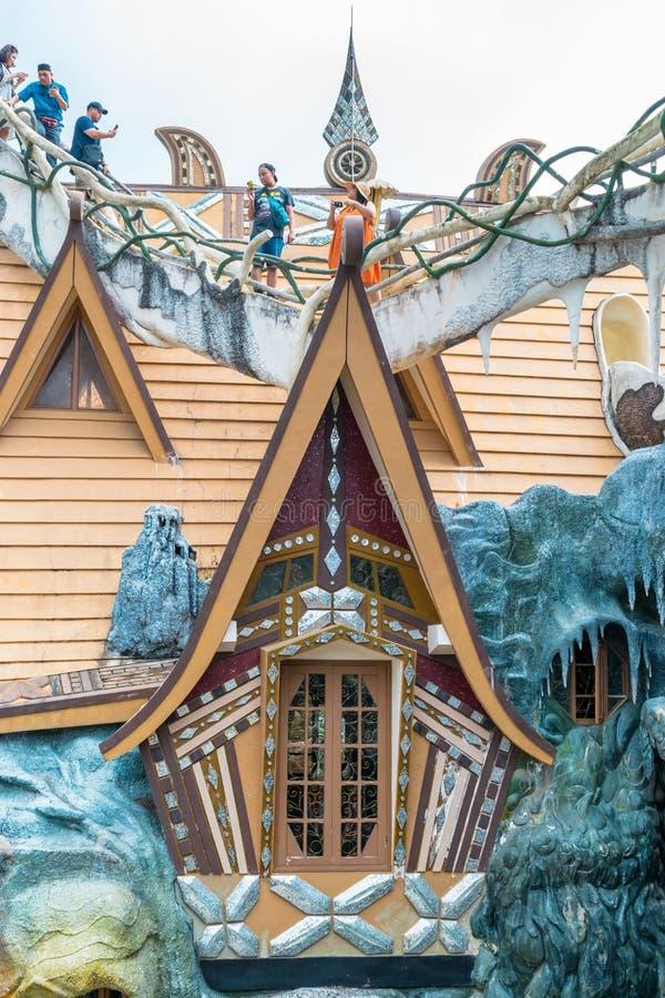 DALAT, VIETNAM - 15 DE ABRIL DE 2019: Los turistas se colocan en el tejado de una casa de madera con una ventana fotos de archivo