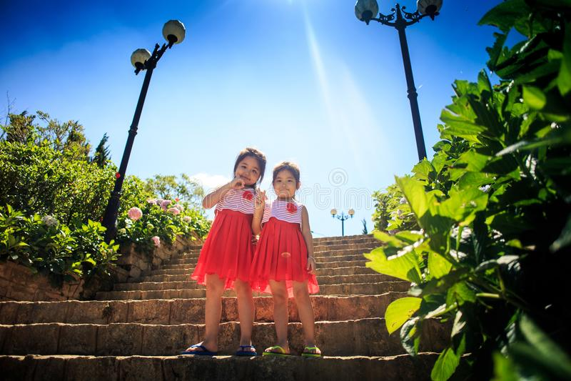 Asian Pretty Girls in Holiday Dresses on Stone Steps by Plants. DALAT/VIETNAM - MAY 16 2016: Vietnamese pretty girls in holiday red and white dresses on stone royalty free stock photos