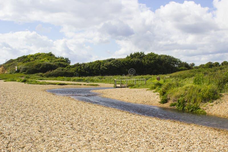 Daleki drewniany footbridge przy końcówką haczyka pasa ruchu uzdy ścieżka blisko Titchfield błonia Anglia zdjęcie stock