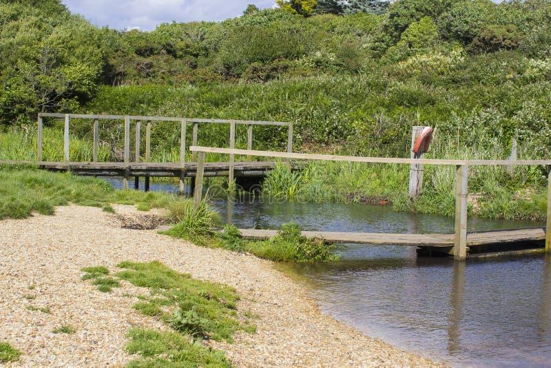 Daleki drewniany footbridge przy końcówką haczyka pasa ruchu uzdy ścieżka blisko Titchfield błonia Anglia obraz stock
