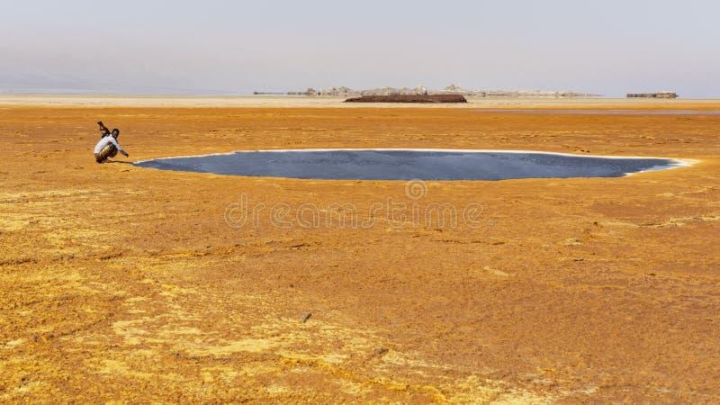 Daleko żołnierz przy Czarnym basenem przy Dallol w Danakil depresji, Afryka zdjęcia royalty free