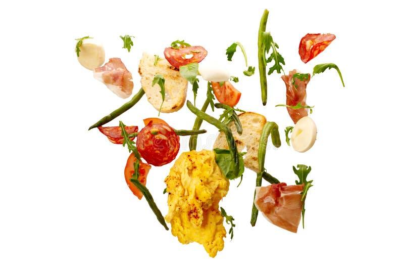 Dalende groenten Plakken van tomaat, eieren, asperge, arugula, salami, prosciutto en toost verse saladeingrediënten in de lucht royalty-vrije stock afbeeldingen
