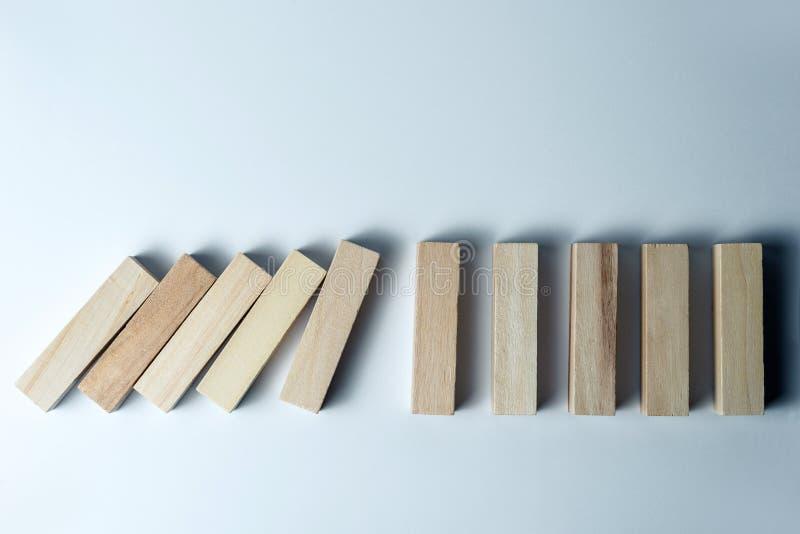 Dalende houten kubussen, als symbool van nederlaag, verkeerde besluit en instorting, betreffende een ongelijke witte achtergrond  stock foto