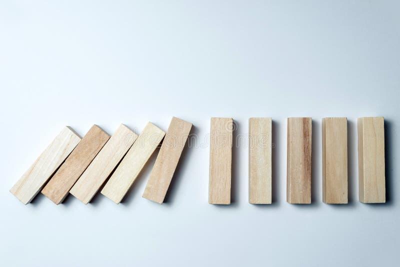 Dalende houten kubussen, als symbool van nederlaag, verkeerde besluit en instorting, betreffende een ongelijke witte achtergrond  royalty-vrije stock afbeeldingen