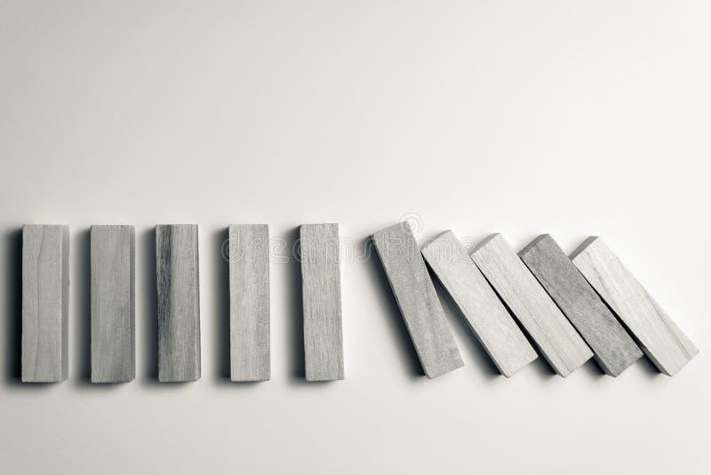 Dalende houten kubussen, als symbool van nederlaag, verkeerde besluit en instorting, betreffende een ongelijke witte achtergrond  royalty-vrije stock afbeelding